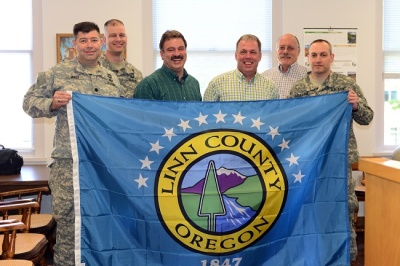 Oregon Army National Guard officers and Linn County commissioners pose with a flag for deployment to Afghanistan. From left to right are; Lt. Col. Daniel Miner, commander of 1-82nd Cavalry Squadron; Maj. Brian Dukes, operations officer for 2-162 Infantry Battalion; Commissioner John Lindsey; Commissioner Roger Nyquist; Commissioner Will Tucker; and Lt. Col. Scot Caughran, commander of 2-162 Infantry Battalion. (Photo by Sgt. 1st Class April Davis, Oregon Military Department Public Affairs)